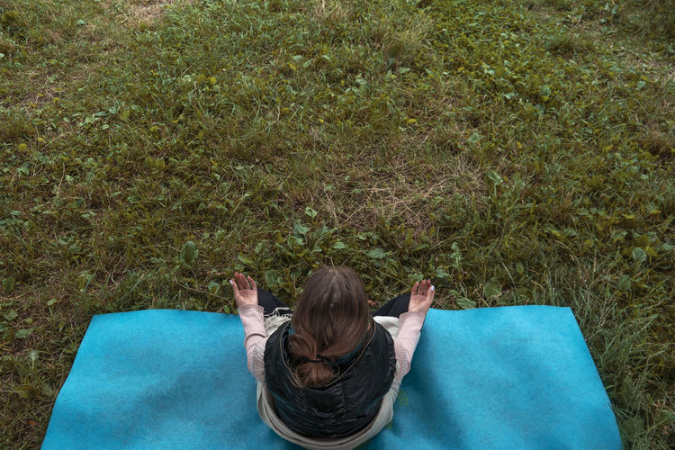 Rear view of woman lying on grass