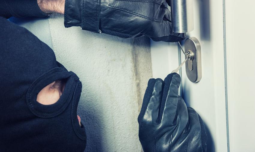 Close-up of thief breaking door lock