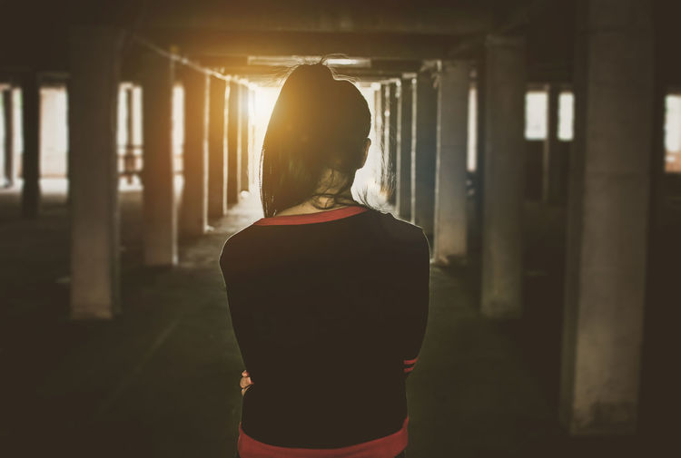 Rear View Of Woman Standing At Abandoned Building