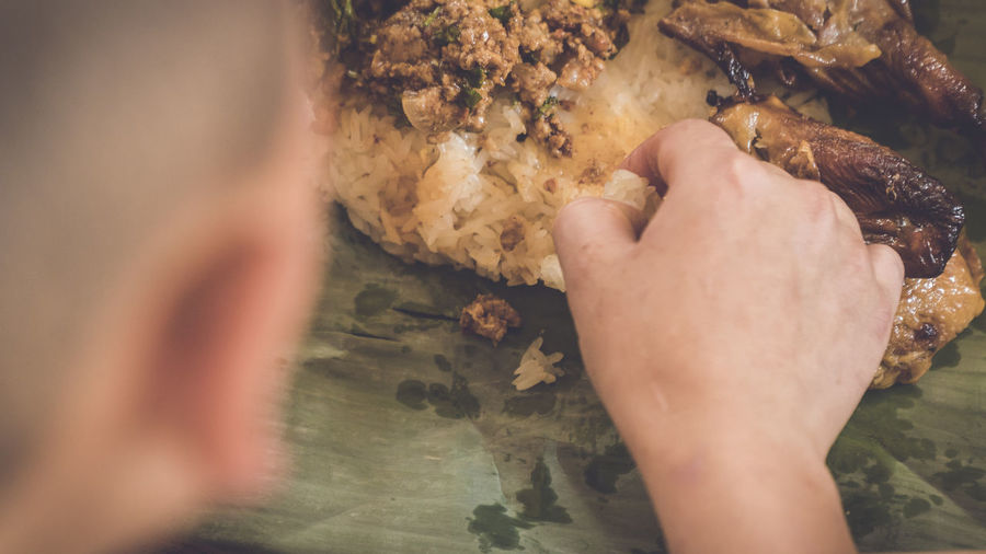 Close-up of person hand eating food in banana leaf