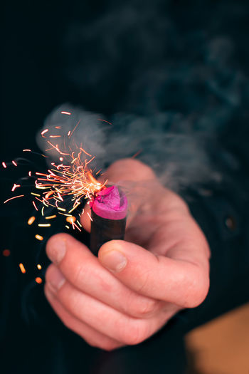 Cropped hand of person holding firecracker
