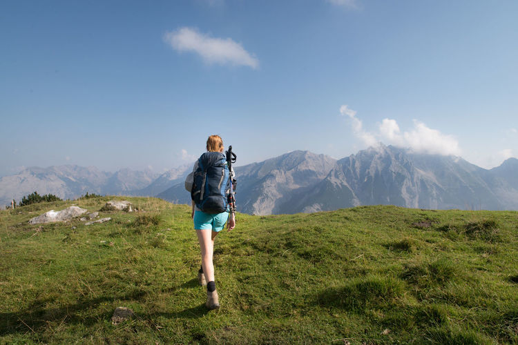 Rear View Of Woman Hiking On Mountain Against Blue Sky