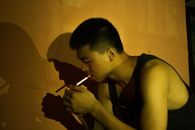 Side View Of Man Lighting Cigarette Against Wall