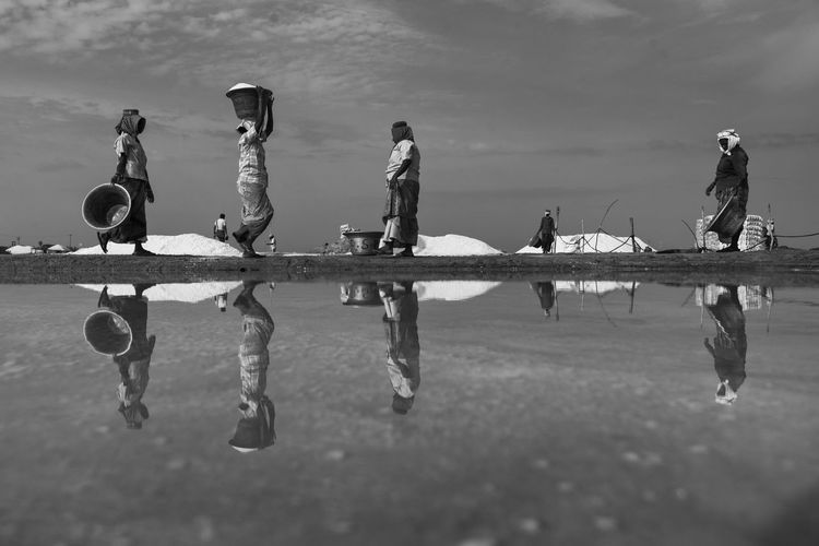 Workers At Salt Flat Against Sky