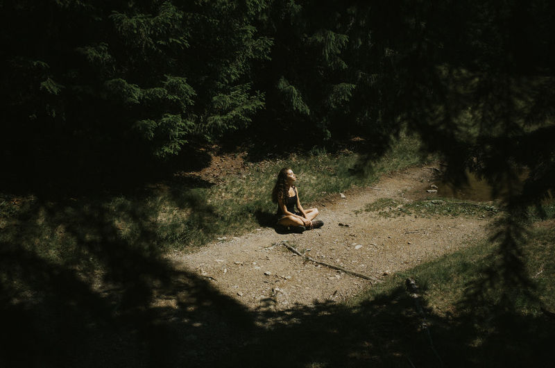 Full Length Of Woman Sitting On Field Amidst Trees