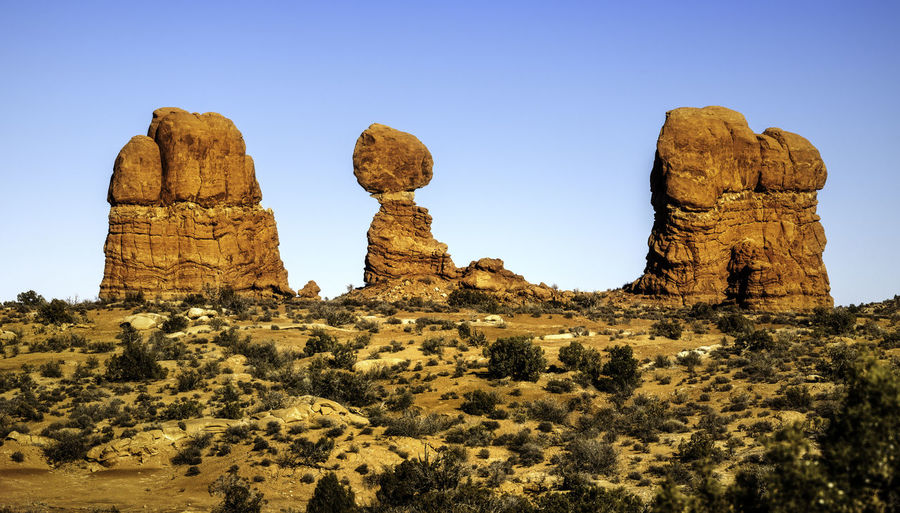 View of rock formations on landscape against clear sky