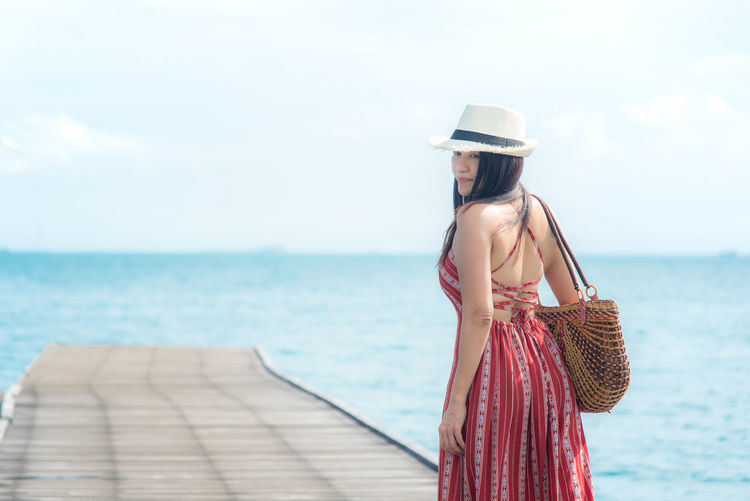Young woman looking at sea against sky