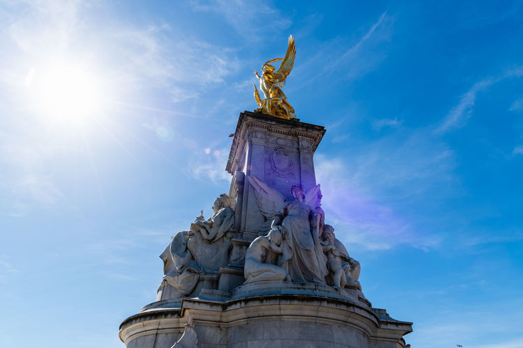 Victoria Memorial Sculpture in front of Buckingham Palace a sunny day against blue sky Brexit Britain Buckingham Buckingham Palace London Queen Uk British Capital City Culture Destinations Elizabeth England English Europe European  Famous Great Guard Historic History KINGDOM Landmark Memorial Monarchy Monument Old Palace People Place Royal Royalty Sculpture Sightseeing Sky Statue Sunny Tourism Tourist Tradition Traditional Travel United Weather Westminster Victoria Memorial Representation