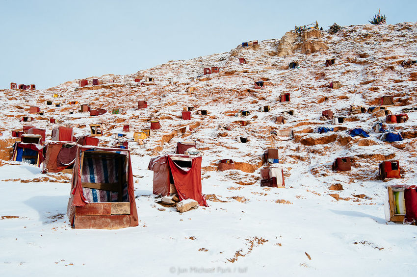 Study boxes are scattered across a hilltop. Tibetan monks and nuns go inside them and read Buddhist teachings. They are humbly made of wooden plates and tarp, and barely shield the occupant from winter cold and wind. 03.03.10. A Journey To Nirvana China Documentary Documentary Photography Jun Michael Park Landscape Photojournalism Reportage Sichuan Snow Tibet Tibetan Buddhism Travel Travel Photography Winter Yarchen Gar
