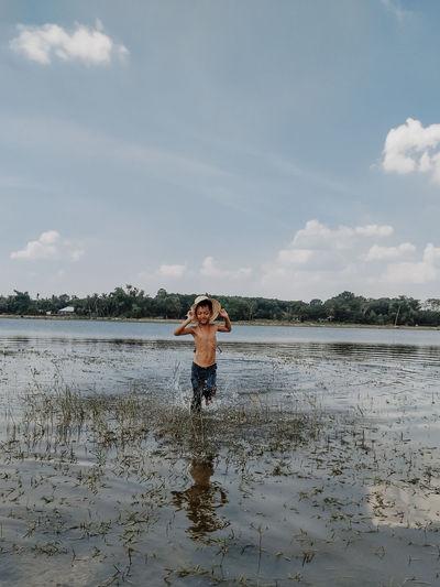 Portrait of man standing in water against sky