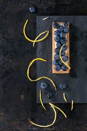 Square Lemon tartlet with fresh blueberries, served on black stone slate with lemon zest over black background. Flat lay. With space for text Berries Black Background Desserts Lemon Tarte Shortbread Berry Tartlet Blackberry Blueberry Blueberry Tart Directly Above Food Lemon Zest Pastry Shortbread Tartlet Slate Sweet Food Tart - Dessert Tartlet Top View Of Food