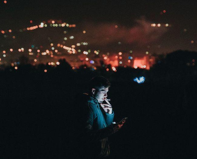 Man smoking while using phone in city at night