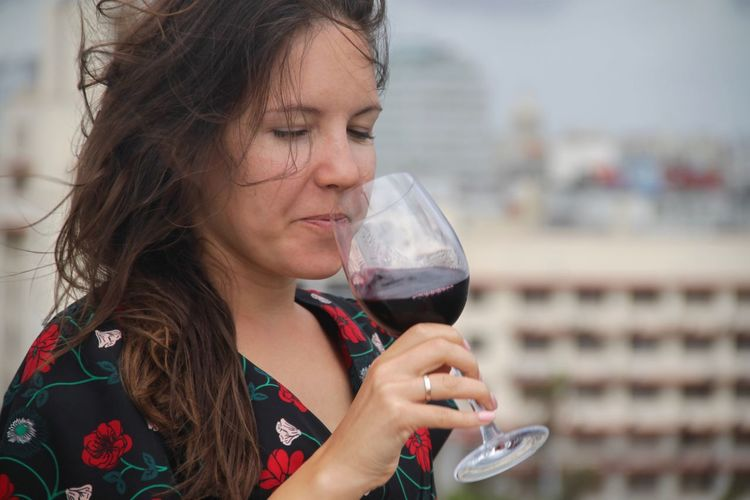 Close-Up Of Woman Drinking Red Wine In City