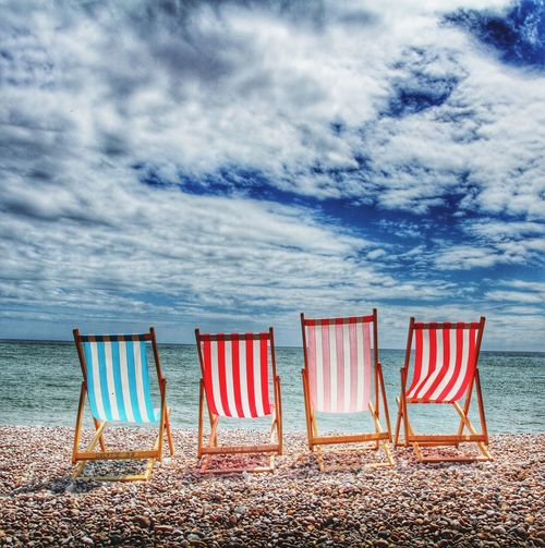 Four deckchairs sitting on a pebble beach with a seaview Deckchairs Chairs Beach Pebble Beach Holiday Vacation Seaside Travel Tourism Rest Relax Relaxation Relaxing Time Resort Relaxing Moments
