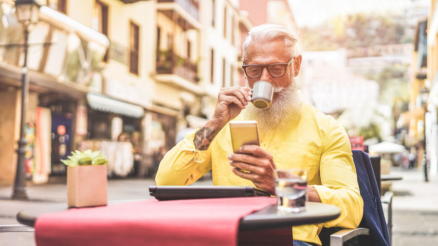 Happy trendy man drinking coffee and using smartphone in bar cafeteria outdoor Coffee Fashion Man Smart Adult Beard Businessman Drink Drinking Eyeglasses  Hipster Male Mobile Phone One Person Phone Senior Smartphone Tattoo Technology Using Phone