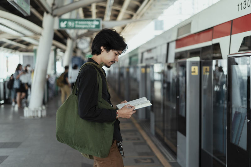 Side view of man reading book while standing at railroad station