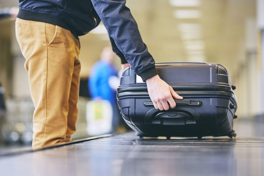 Traveler picking up suitcase from baggage claim in airport terminal. Logistics Man Passenger Picking Up Travel Airport Airport Terminal Baggage Baggage Claim Carousel Focus On Foreground Hand Holding Human Body Part Journey Low Section Luggage People Real People Sorting  Suitcase Tourism Transportation Traveler Wheeled Luggage