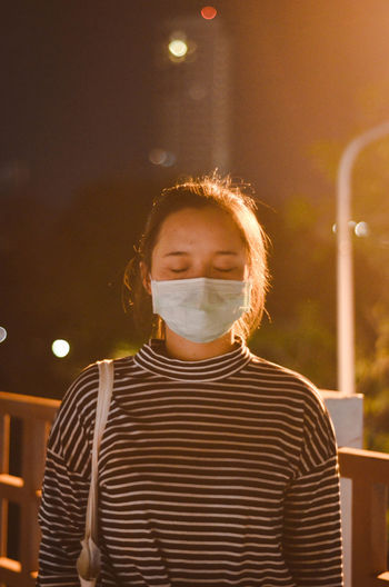 Young woman wearing pollution mask at night