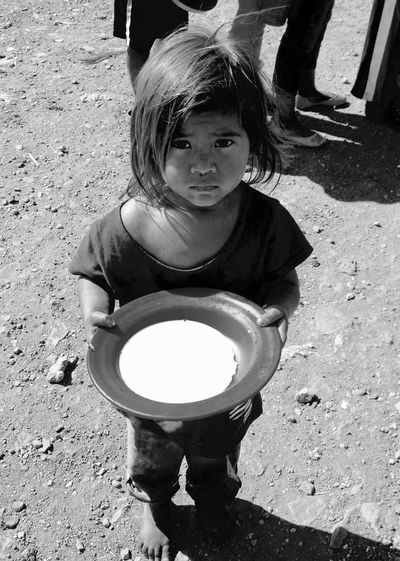 I took this picture while volunteering at an NGO, In a very poor area of Honduras , my home town. I love this picture. I think it expresses a lot. This plate of oatmeal was probably the first thing this baby girl had eaten. Beautiful Girl Photograph Photography Hope4honduras Takenbyme Black&white