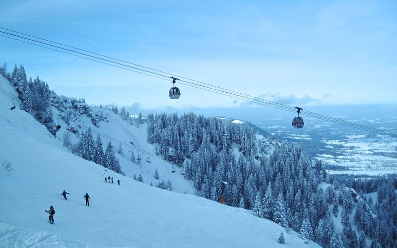 People On Snow Covered Mountains By Ski Lift Against Sky