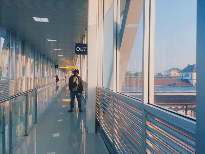 Man standing in corridor of building