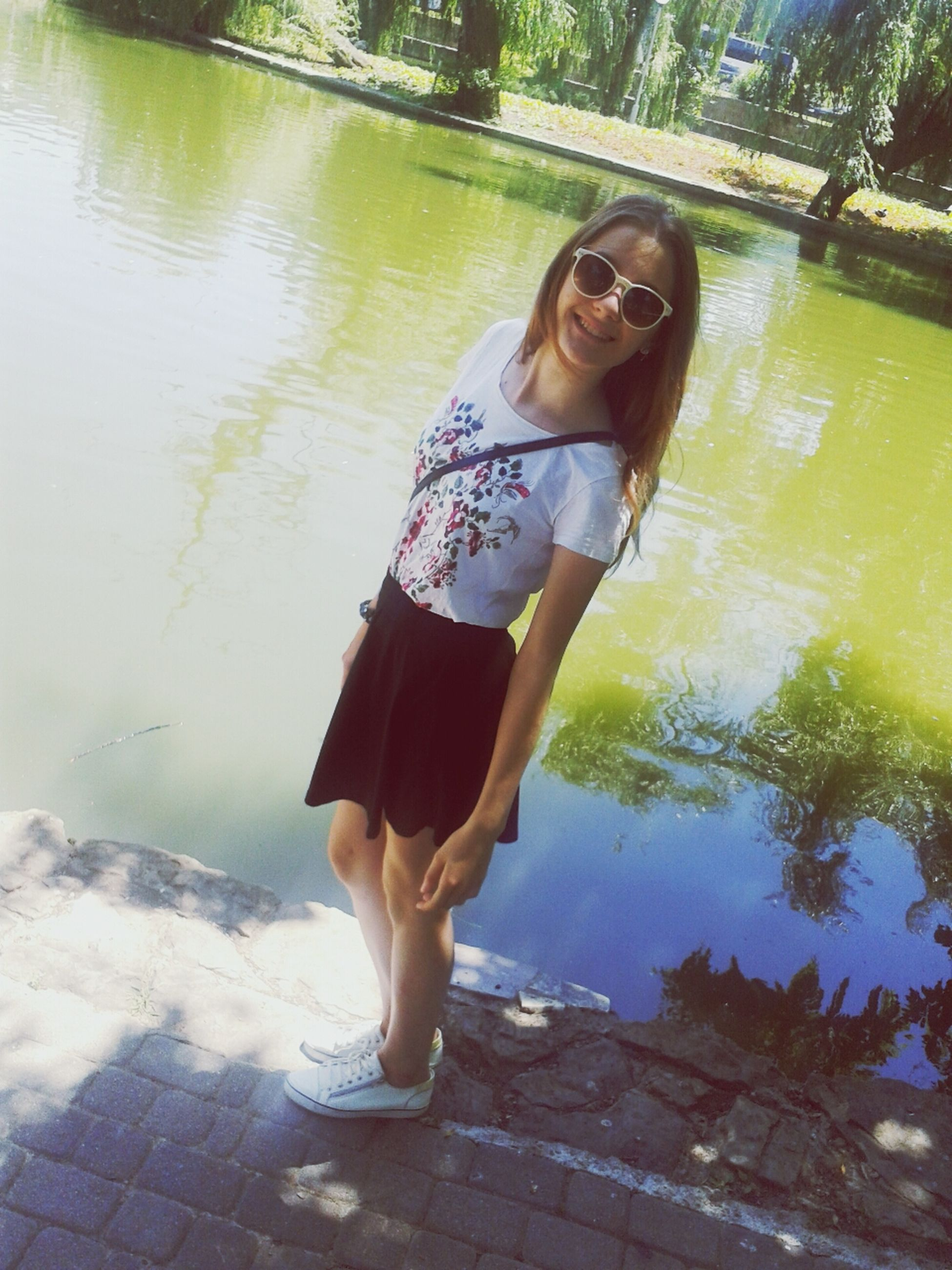 water, lifestyles, person, lake, leisure activity, young adult, casual clothing, full length, standing, reflection, young women, three quarter length, portrait, looking at camera, day, front view, high angle view, sitting