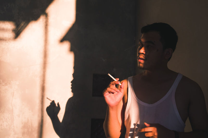 Young man holding cigarette at home