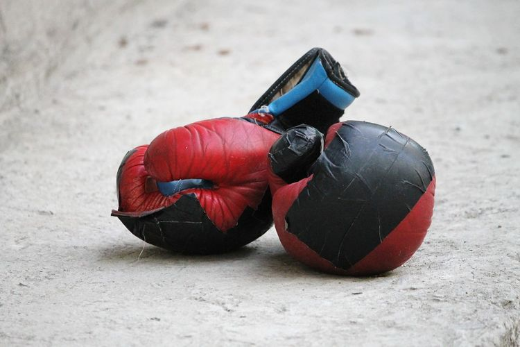 High Angle View Of Boxing Gloves On Footpath