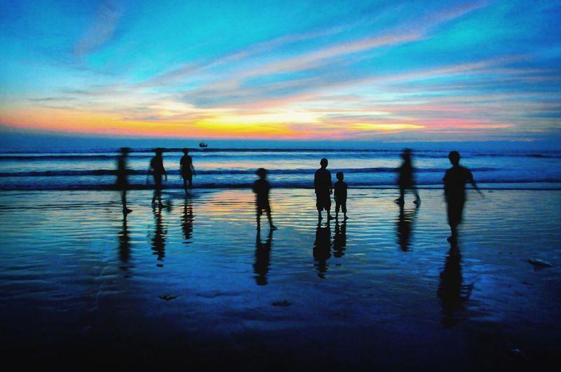 Silhouette Children Enjoying At Beach During Sunset