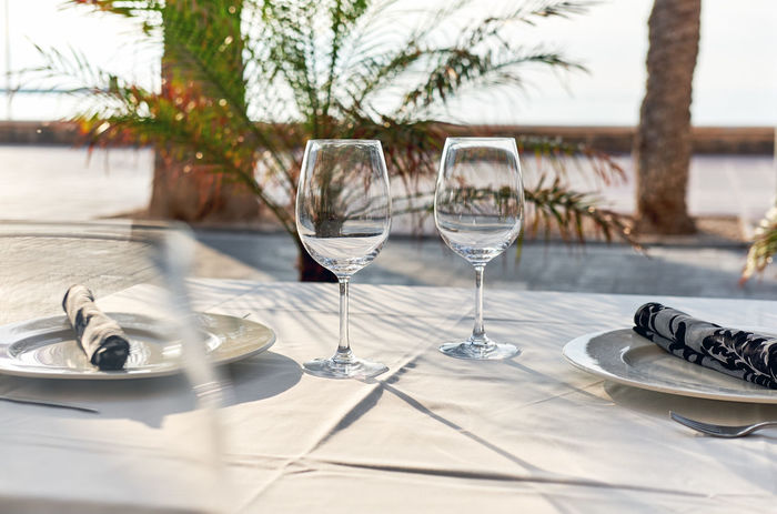 Table setting with a wine glasses, cutlery and plates. Outdoors restaurant. Tropical landscape Dinner Outdoors Restaurant SPAIN Table Setting Table Arrangements Tableware Crockery Dining Table Drink Drinking Glass Empty Glasses Empty Restaurant Food And Drink Glass Idyllic No People Open Air Restaurant Outdoors Palm Trees Restaurant Still Life Table Table Appointments Wineglass Wineglasses