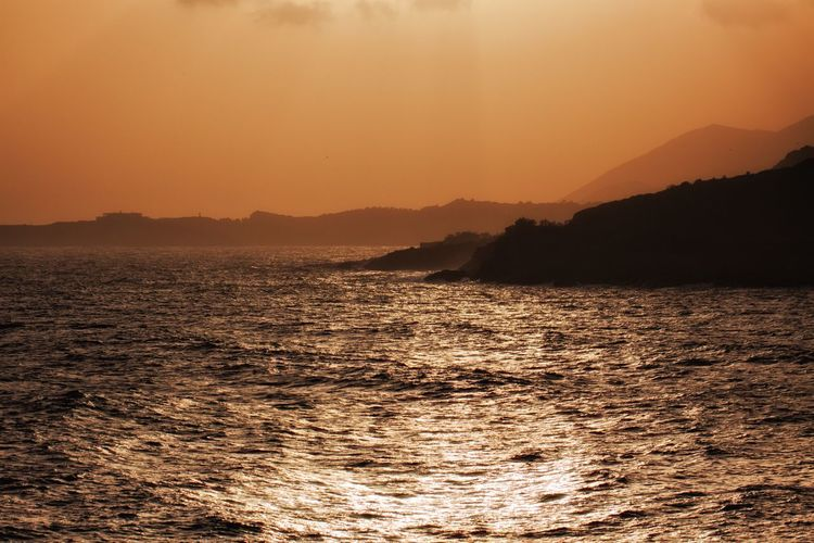 Scenic sea view from the Temple of Poseidon. Sky Beauty In Nature Sunset Scenics - Nature Water Tranquility Tranquil Scene Mountain Orange Color Waterfront Nature Sea No People Idyllic Silhouette Non-urban Scene Outdoors Remote Sunlight