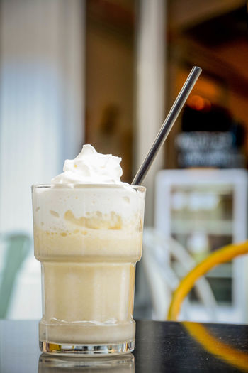 Close up view of banana shake Banana Shake Close-up Dairy Product Drink Drinking Glass Drinking Straw Focus On Foreground Food Food And Drink Freshness Glass Household Equipment Indoors  Indulgence No People Ready-to-eat Refreshment Still Life Straw Sweet Sweet Food Table Temptation