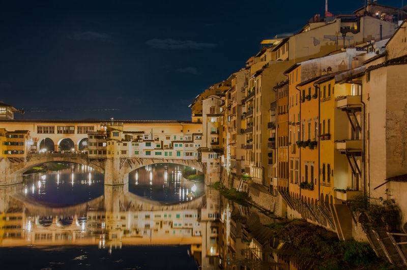 Ponte Vecchio Over Arno River Against Sky In City At Night