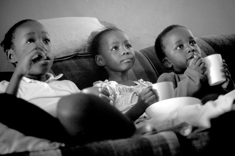 Low Angle View Of Siblings Sitting On Sofa While Watching Tv At Home