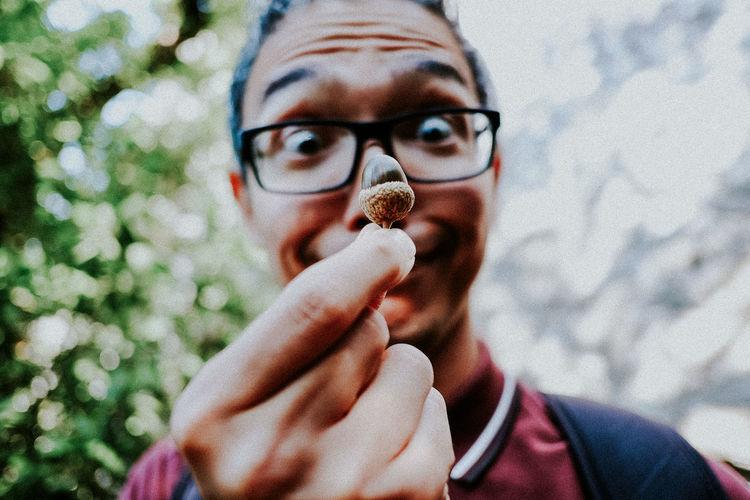 Close-up of man looking at hazelnut