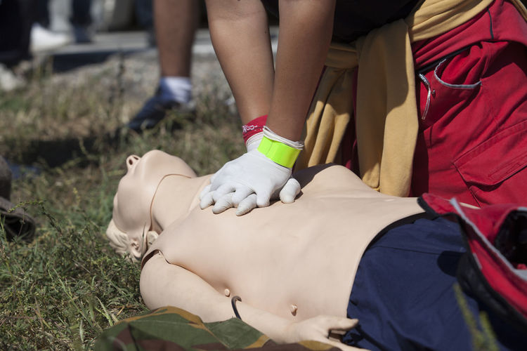 Low section of man practicing cpr on dummy at field during sunny day