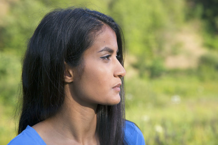 Close-up of thoughtful woman on field