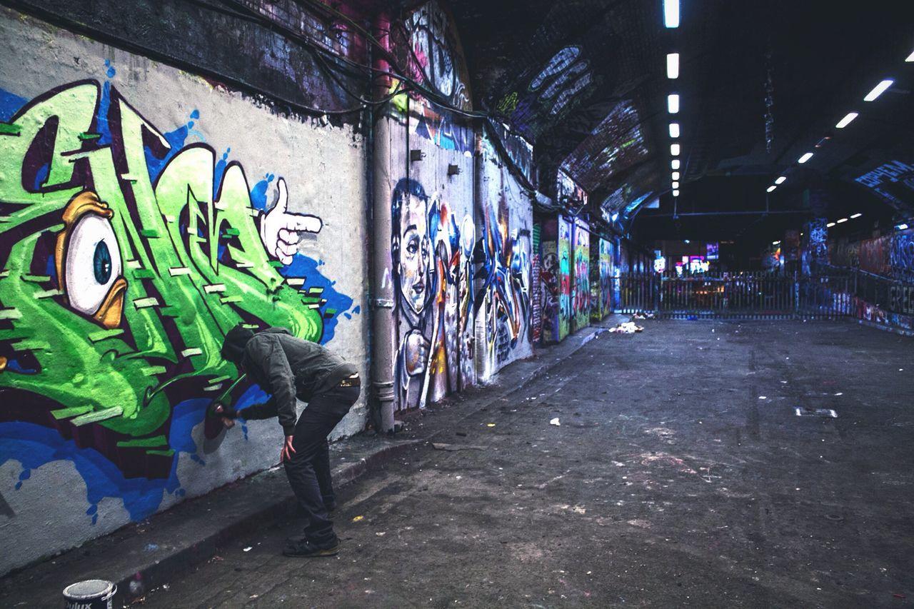 Man Drawing Graffiti On Wall