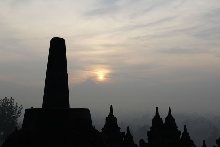 Silhouette Borobudur Temple with the mysteries forest surrounding during sunrise, Yogyakarta, Indonesia Ancient Borobudur Temple Java Yogyakarta Ancient Civilization Architecture Buddhism Built Structure Cloud - Sky Dawn Fog Forest History Memorial Mount Merapi No People Outdoors Place Of Worship Religious Architecture Silhouette Sky Sunrise Sunset The Past Travel