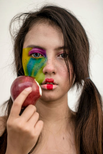 Close-up portrait of woman wearing make-up while having apple at home