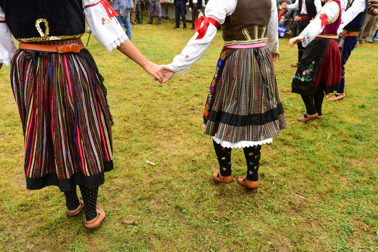 Low section of people wearing traditional clothing while holding hands on grass