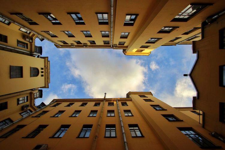 Directly Below Shot Of Buildings Against Cloudy Sky