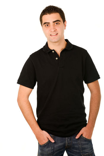 Portrait of young man smiling while standing against white background