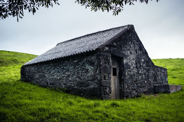 Built structure on field against sky
