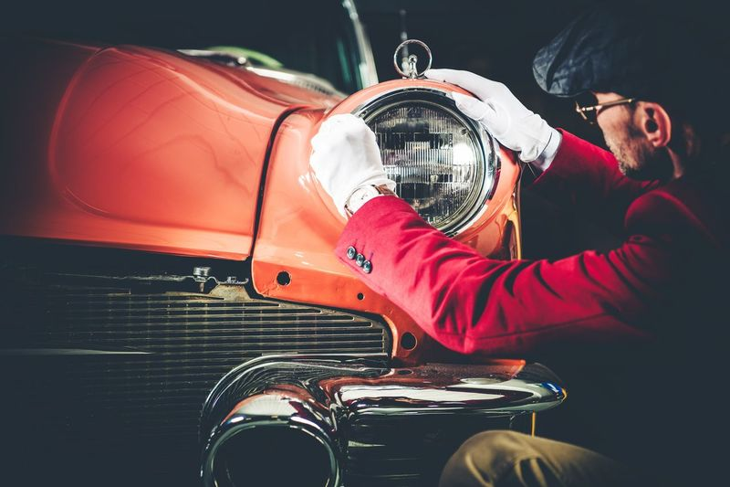 Side View Of Man Checking Vintage Car Headlight