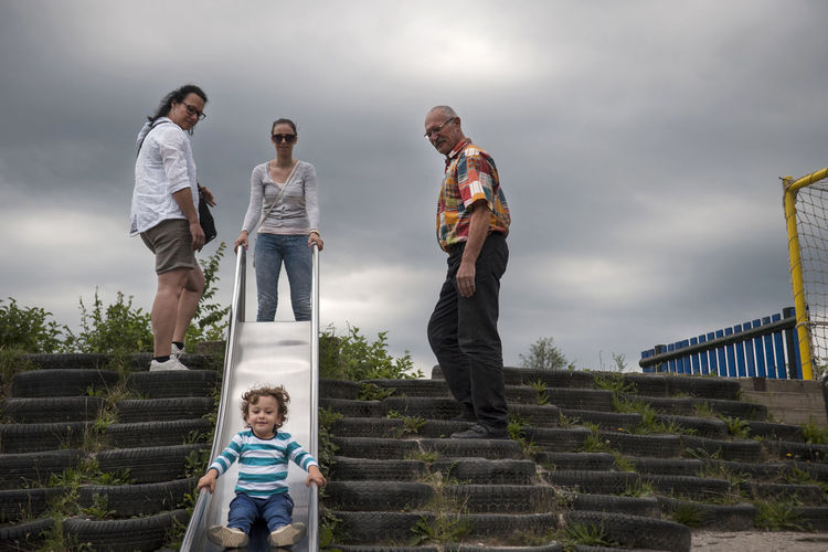 Family with cute boy at playground against sky