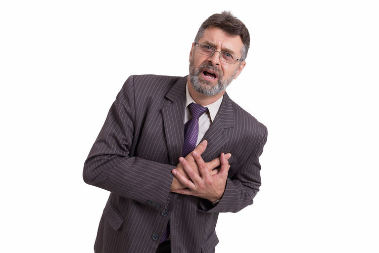 Portrait of businessman with heart attack standing against white background