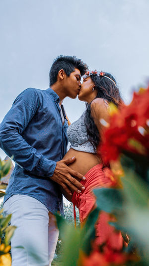 Low Angle View Of Expectant Couple Kissing While Standing Against Sky
