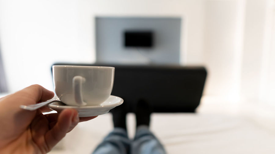 Midsection of person holding coffee cup