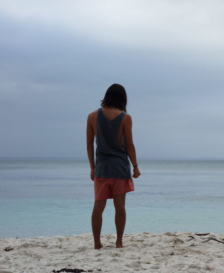 Beach Beauty In Nature Casual Clothing Full Length Hairstyle Horizon Horizon Over Water Land Leisure Activity Lifestyles One Person Outdoors Real People Rear View Sand Scenics - Nature Sea Sky Standing Water